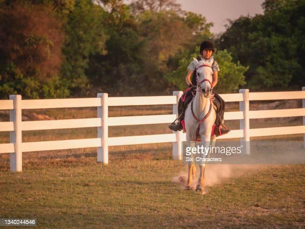 young asian girl enjoy riding horse
