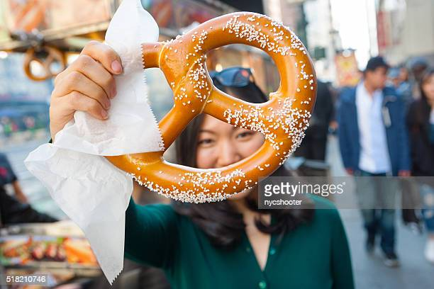 Young asian girl holding pretzel in NYC