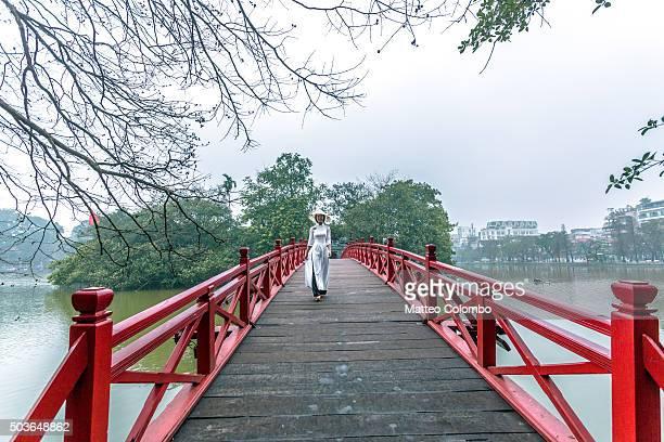 Young asian girl in Ao Dai dress on famous bridge, Hanoi, Vietnam