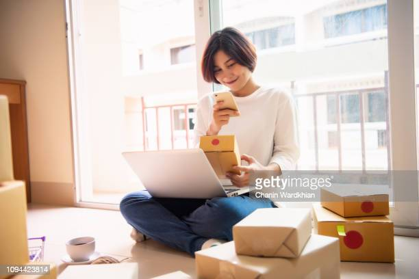 Young asian girl is freelancer with her private business at home office, Working with laptop, Coffee, Online marketing, Customer order and packaging or packing