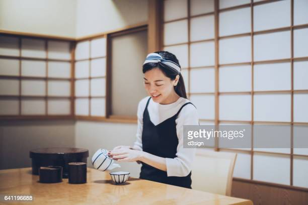 Young Asian girl is pouring a cup of tea in traditional Japanese room