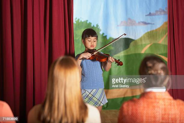 Young Asian girl playing violin at recital