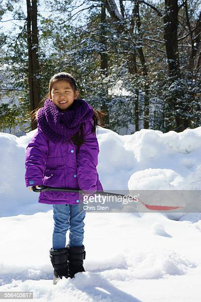 young asian girl showeling snow - scarsdale stock photos and pictures