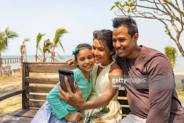 Young Asian Girl Taking a Selfie on Vacation With Her Parents