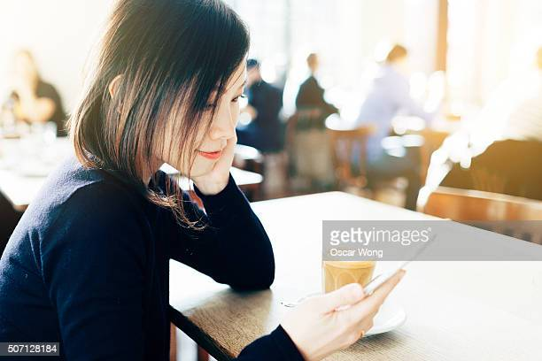 Young Asian girl using mobile phone in cafe