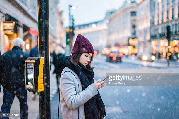 Young asian girl using smartphone on the street