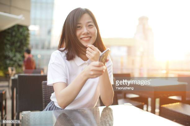 Young asian girl using the phone at Shanghai downtown,background is Lujiazui commerical center,China