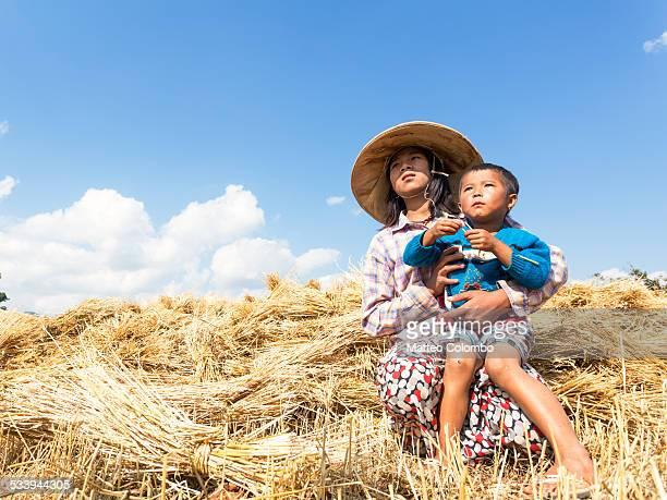 Young asian girl with baby boy in a crop field