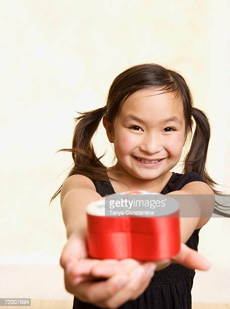 Young Asian girl with heart box in outstretched hands