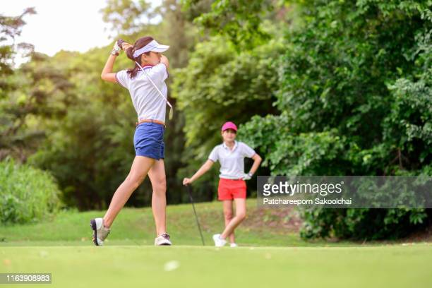 young asian golfer playing golf in golft course, healthy sport - 女子 ゴルフ ストックフォトと画像