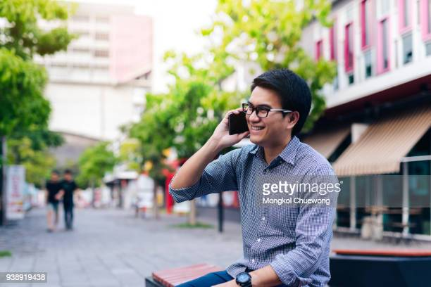 Young asian handsome businessman happy smiling while using his smartphone. Portrait of asian business man using message with smart phone in outdoor.