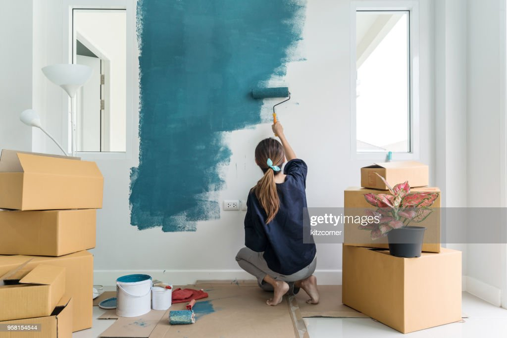 Young asian happy woman painting interior wall : Stock Photo