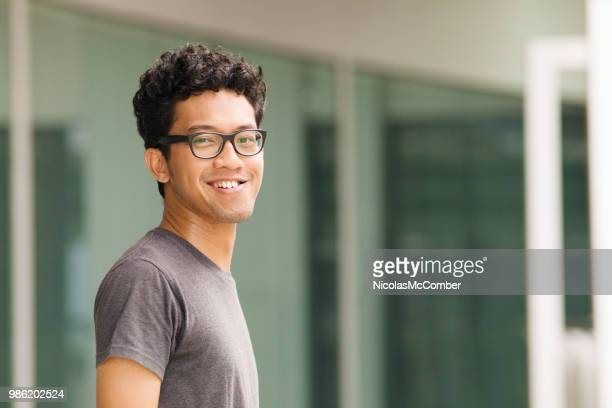 young asian intellectual man urban sideways turning portrait with eyeglasses - turning stock pictures, royalty-free photos & images