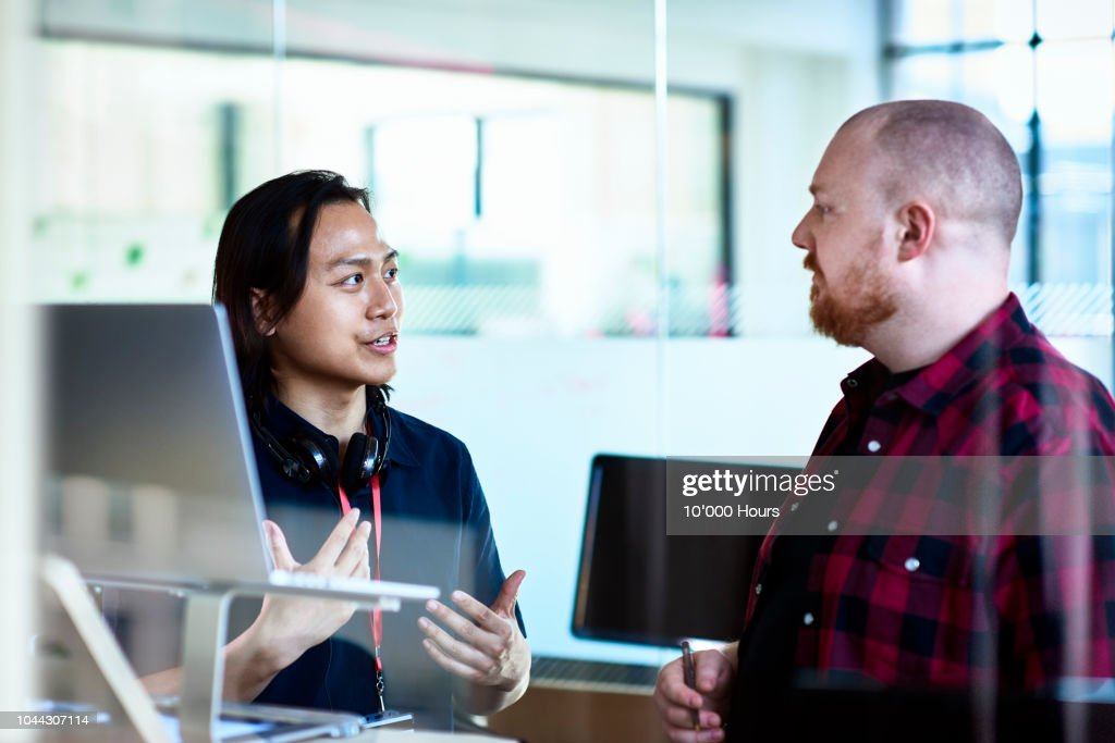 Young Asian IT consultant advising manager in office : Stock Photo