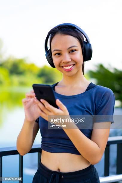 giovane jogger asiatico che usa lo smartphone e ascolta la musica. - filippine foto e immagini stock