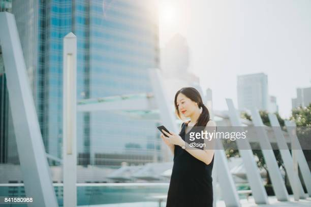 Young Asian lady checking emails on smartphone in urban city
