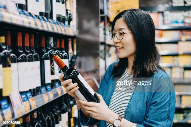 young asian lady choosing and looking at bottle of wine in wine store - liquor store stock pictures, royalty-free photos & images