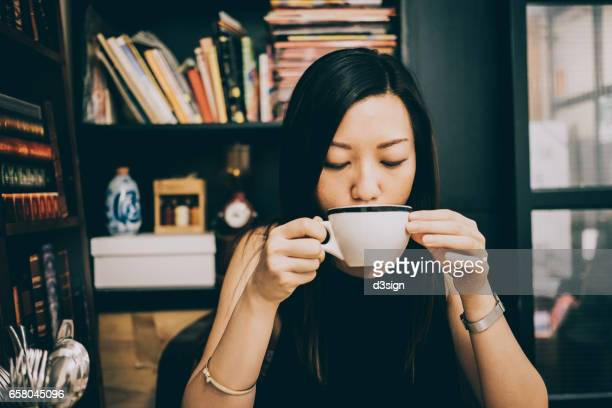 Young Asian lady having a relaxing coffee time in cafe