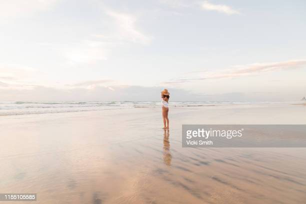 young asian lady in bikini and with a hat walking on the beach at sunrise - gold coast queensland stock pictures, royalty-free photos & images
