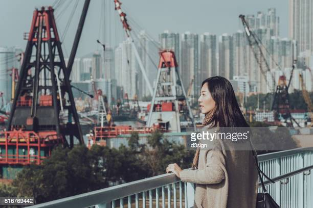 Young Asian lady overlooking cityscape of Hong Kong on urban balcony