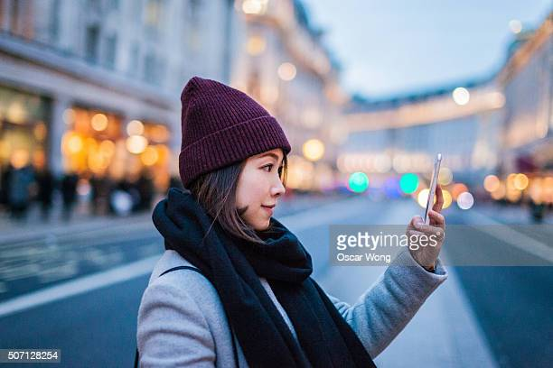 Young asian lady taking picture on the high street