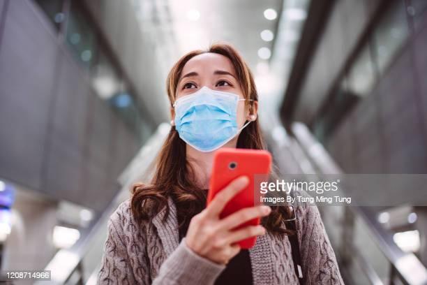 young asian lady using smartphone joyfully in train station - bahnreisender stock-fotos und bilder