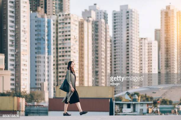 Young Asian lady walking in the city, with layers of highrise buildings in the background