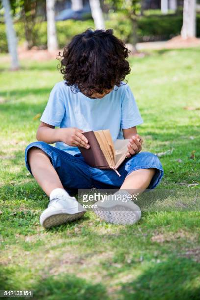Young asian little boy reading a book outdoors