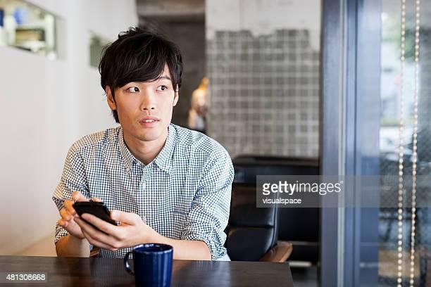若いアジア窓辺の間に彼の電話