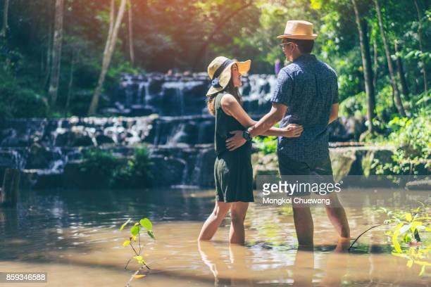 Young asian love couple traveler relaxing in greens jungle and enjoying view in waterfall. Namtok Sam Lan Waterfall, Saraburi, Thailand.