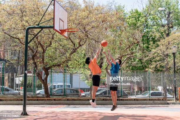 young asian male adults playing basketball outdoors - friendly match stock pictures, royalty-free photos & images