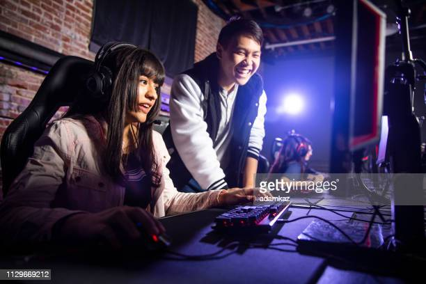 young asian male coaching a woman playing esports - esports stock pictures, royalty-free photos & images