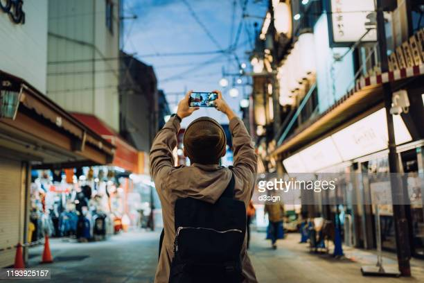 young asian male traveller photographing the vitality of local city street scene with smartphone while travelling in kyoto, japan - travel ストックフォトと画像