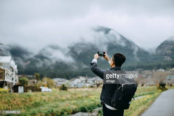 young asian male traveller with backpack photographing the beautiful nature scenics with smartphone while on vacation - tourist ストックフォトと画像