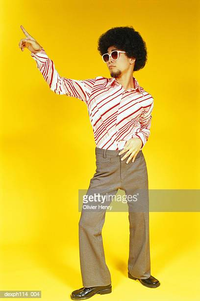 Young Asian male with afro hair gives the 'Staying Alive' pose