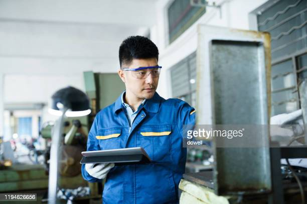 young asian male working on lathe with digital tablet - technician stock pictures, royalty-free photos & images