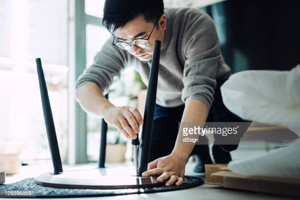 young asian man assembling furniture with a screwdriver, he is setting up a wooden coffee table in newly refurbished apartment against sunlight - furniture stock pictures, royalty-free photos & images