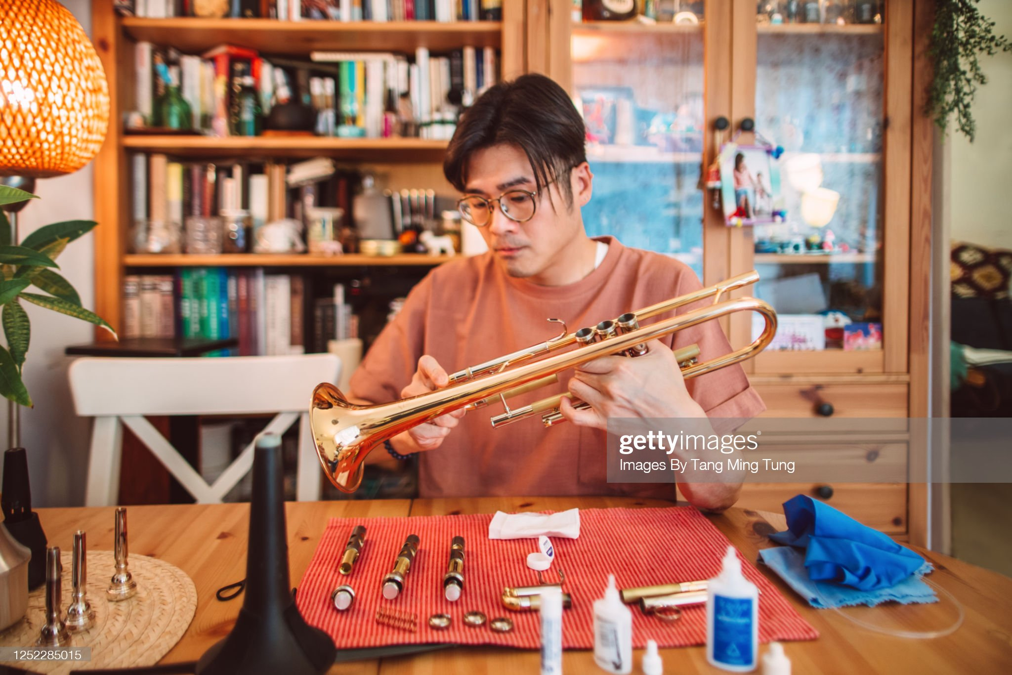 Young Asian man carrying out maintenace work of his trumpet at home : Stock Photo