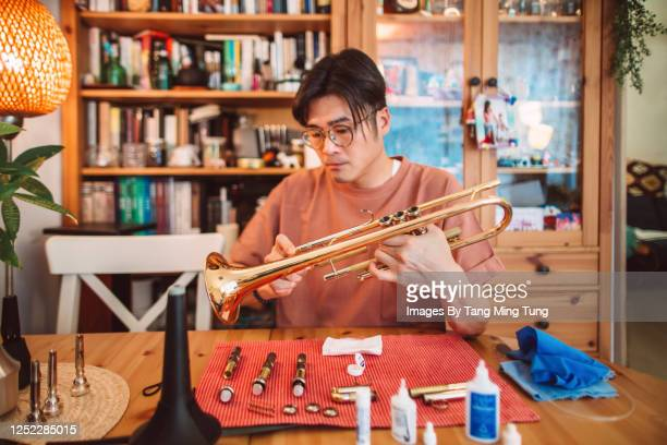 young asian man carrying out maintenace work of his trumpet at home - 趣味 ストックフォトと画像