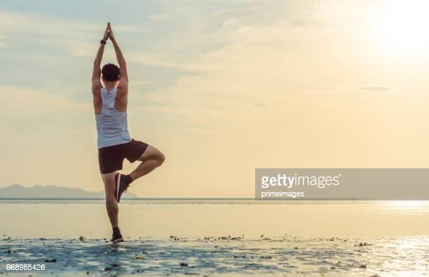 Young asian man doing yoga exercise at sunset beach