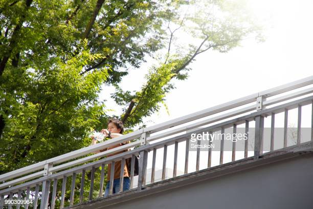 Young asian man drinking water on a footbridge outside.