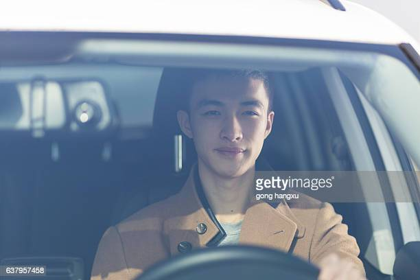 young asian man driver in the car