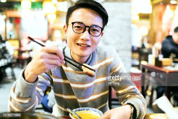 young asian man enjoying chinese food - evening meal ストックフォトと画像