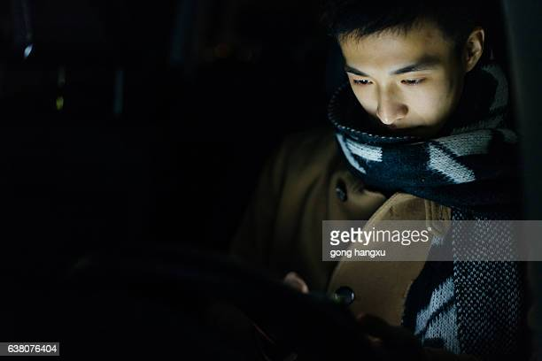 young asian man  hold mobile phone in car at night