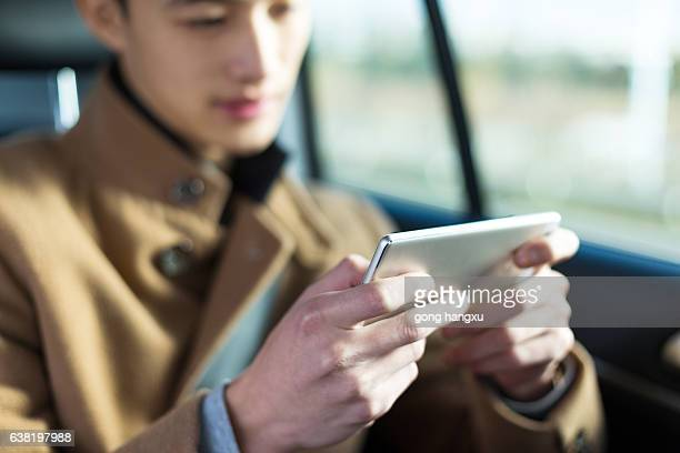 young asian man  hold mobile phone in car