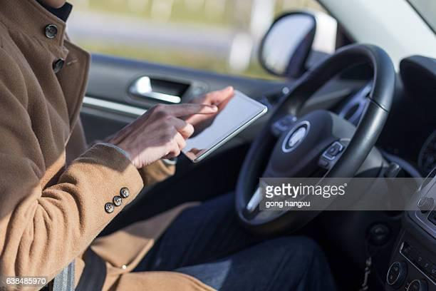 young asian man  hold tablet in car