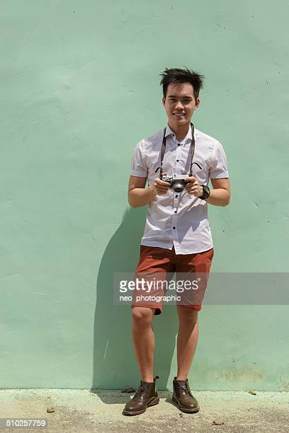 Young Asian man holding digital camera outdoors