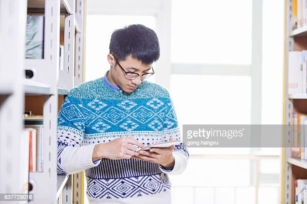 young asian man holds tablet in library