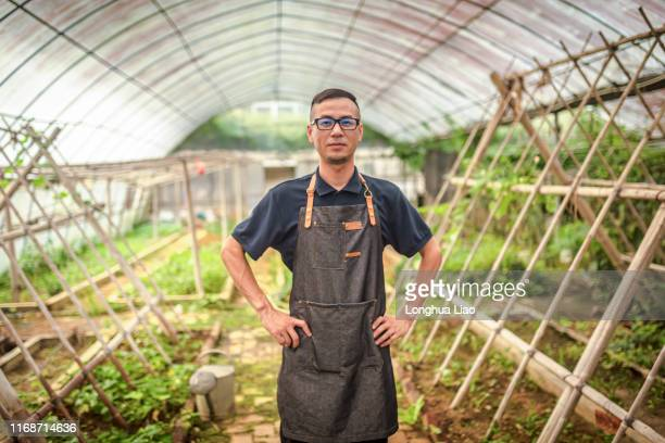 A young Asian man in a greenhouse