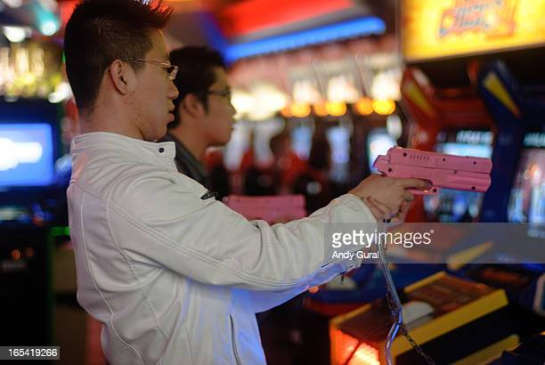 Young Asian man in a white leather jacket takes aim with a pink gun at a video game.